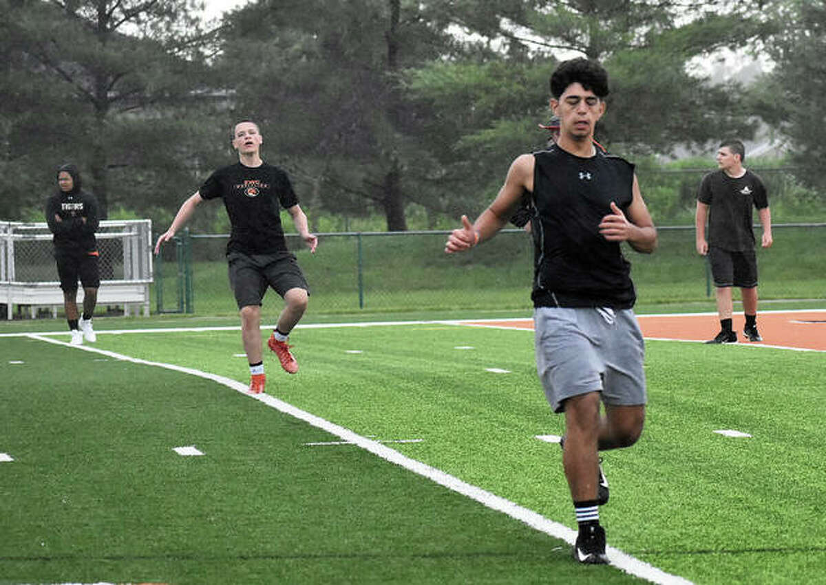 Members of the Edwardsville football team run through the rain during a conditioning session in June inside the District 7 Sports Complex.