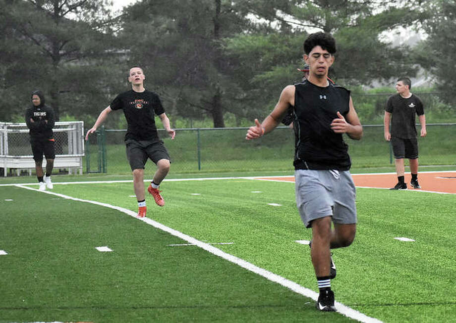 Members of the Edwardsville football team run through the rain during a conditioning session in June inside the District 7 Sports Complex. Photo: Matt Kamp|The Intelligencer