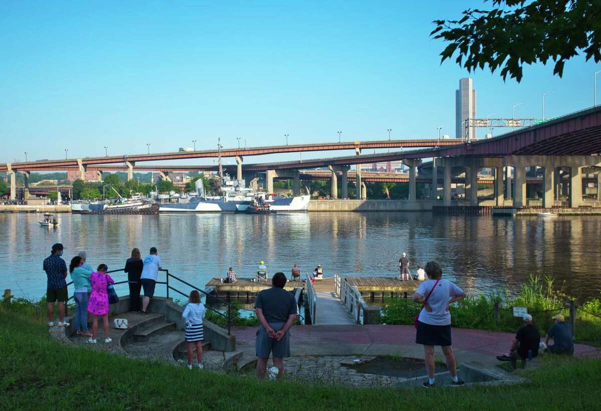 People gather along the Hudson River in Rensselaer to watch the USS Slater depart on Sunday, July 5, 2020, in Albany, N.Y.