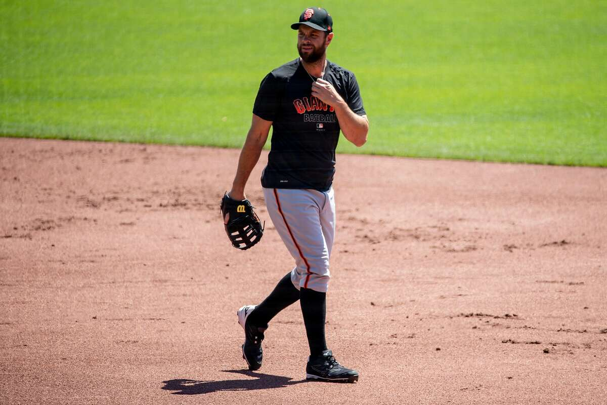 San Francisco Giants infielder Brandon Belt (#9) walks on the field while warming up during the San Francisco Giants' summer training camp session at Oracle Park in San Francisco, Calif. Saturday, July 4, 2020. Due to COVID-19, the 2020 MLB season has been postponed with players just beginning to return for warmups and practices while wearing masks and keeping social distance.