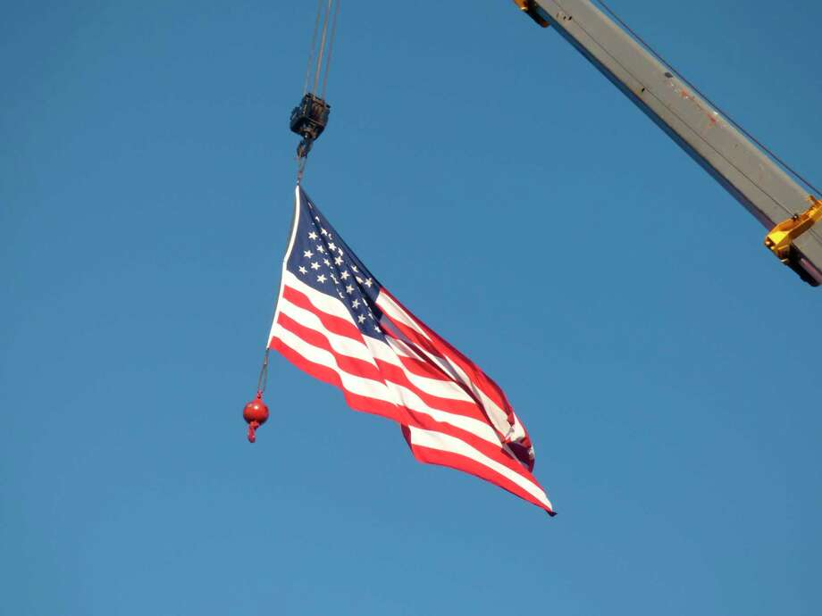 Large flags were elevated by cranes at Manistee Catholic Central and Parkdale Auto for Fourth of July weekend. (Scott Fraley/News Advocate)
