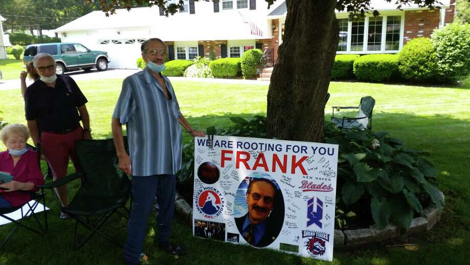 Frank Camera, a longtime pro hockey off-ice official, poses alongside a poster made as part of a car parade this past July. Camera died on Monday. He was 83. Photo: Michael Fornabaio / Hearst Connecticut Media