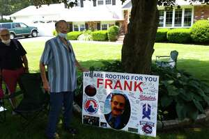Frank Camera, a longtime pro hockey off-ice official, poses alongside a poster made as part of a car parade this past July. Camera died on Monday. He was 83.