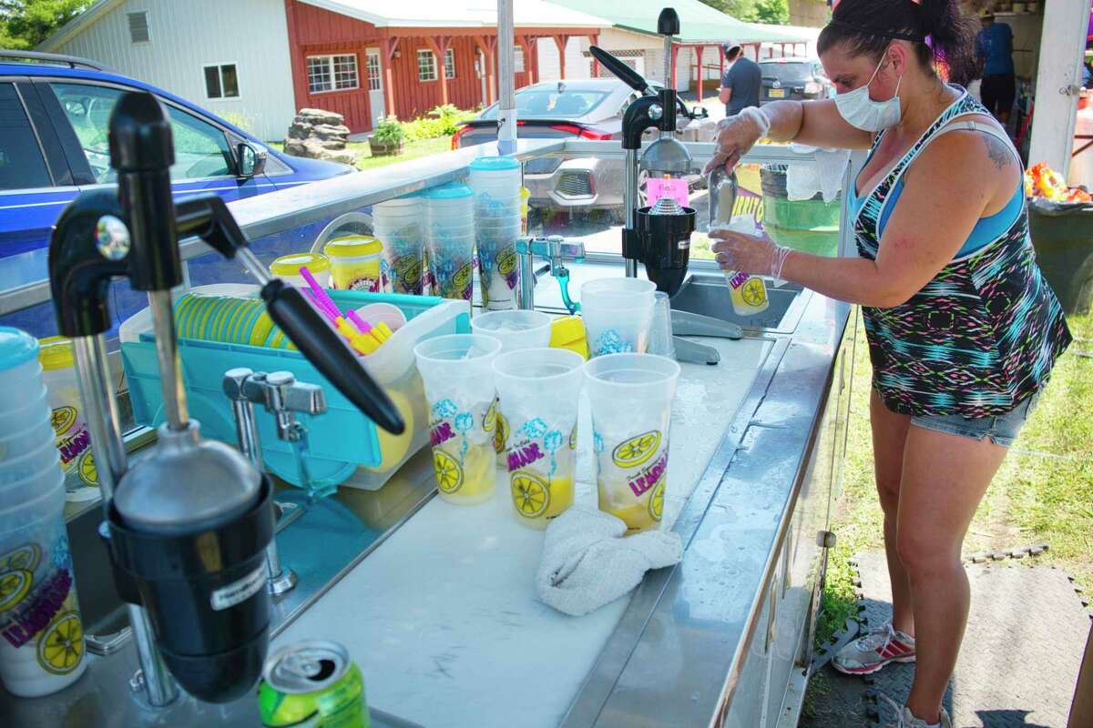 Harmony Thibodeau with Gillette Shows out of Pittsfield, Mass., makes lemonades at The Pit Stop stand for customers in their cars at the Fair Food Fest at the Altamont Fair in July 2020. The food festival was held to give people the chance to enjoy the fair food even though the Altamont Fair was canceled.(Paul Buckowski/Times Union)