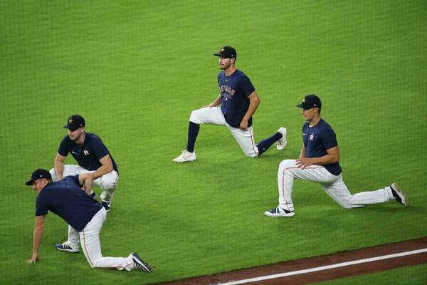 Houston Astros outfielders Myles Straw, from left, Kyle Tucker, catchers Garrett Stubbs and Dustin Garneau warm up during the Astros summer camp Sunday, July 5, 2020, at Minute Maid Park in Houston.
