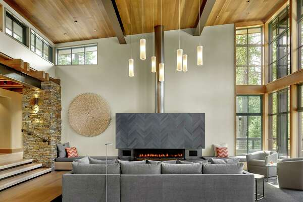 Clerestory windows help illuminate this living room conceptualized by Y.A. Studio that's warmed by a gas fireplace with a herringbone-patterned mantlepiece.