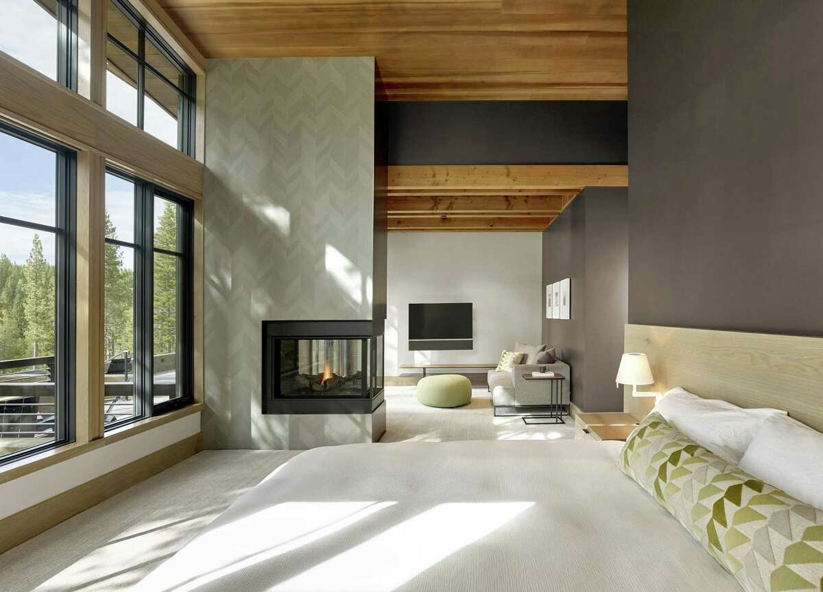 A three-sided gas fireplace warms this bedroom designed by San Francisco's Y.A. Studio.