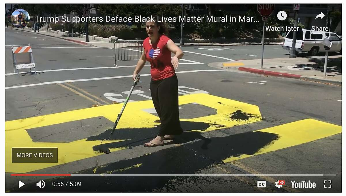 An as-yet unidentified woman paints over a just-finished Black Lives Matter mural painted on the street in front of the Contra Costa County Courthouse in Martinez on Saturday, July 4, 2020. A man with her used his phone to make video of bystanders who challenged their right to paint over the mural.