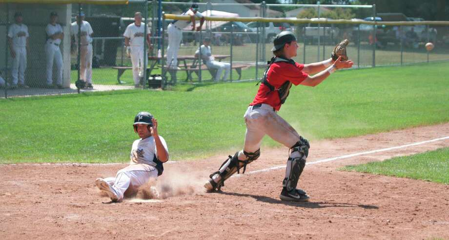 Saints outfielder Logan Briggs slides safely into home during Manistee's doubleheader against the Northern Michigan Dogmen Saturday at Rietz Park. (Kyle Kotecki/News Advocate)