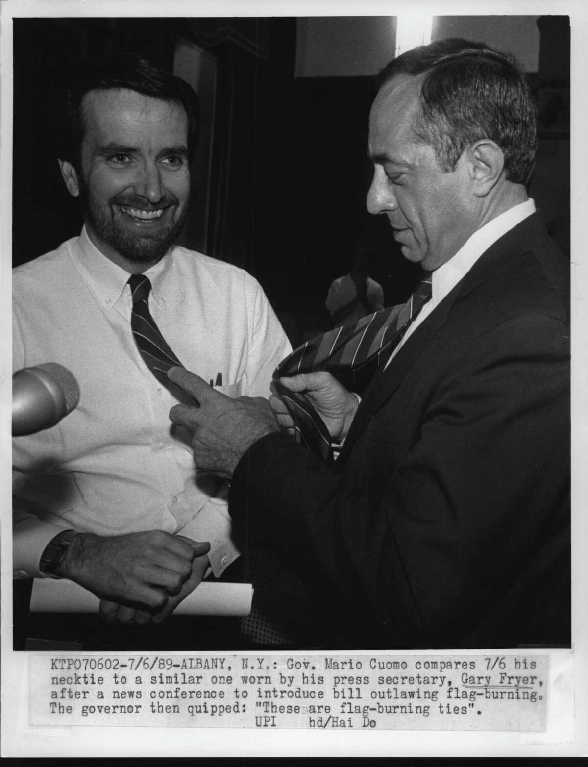 Albany, New York - Governor Mario Cuomo compares 7/6 his necktie to a similar one worn by his press secretary, Gary Fryer, after a news conference to introduce bill outlawing flag-burning. The governor then quipped: