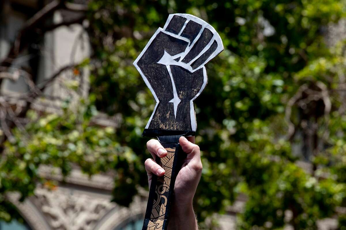 A man carries a sign depicting a Black fist while marching alongside hundreds of demonstrators down Market Street from the Ferry Building in solidarity with the Black Lives Matter movement, calling for the defunding of police, investment in Black communities and the resignation of President Trump held in San Francisco, Calif. Saturday, June 20, 2020.