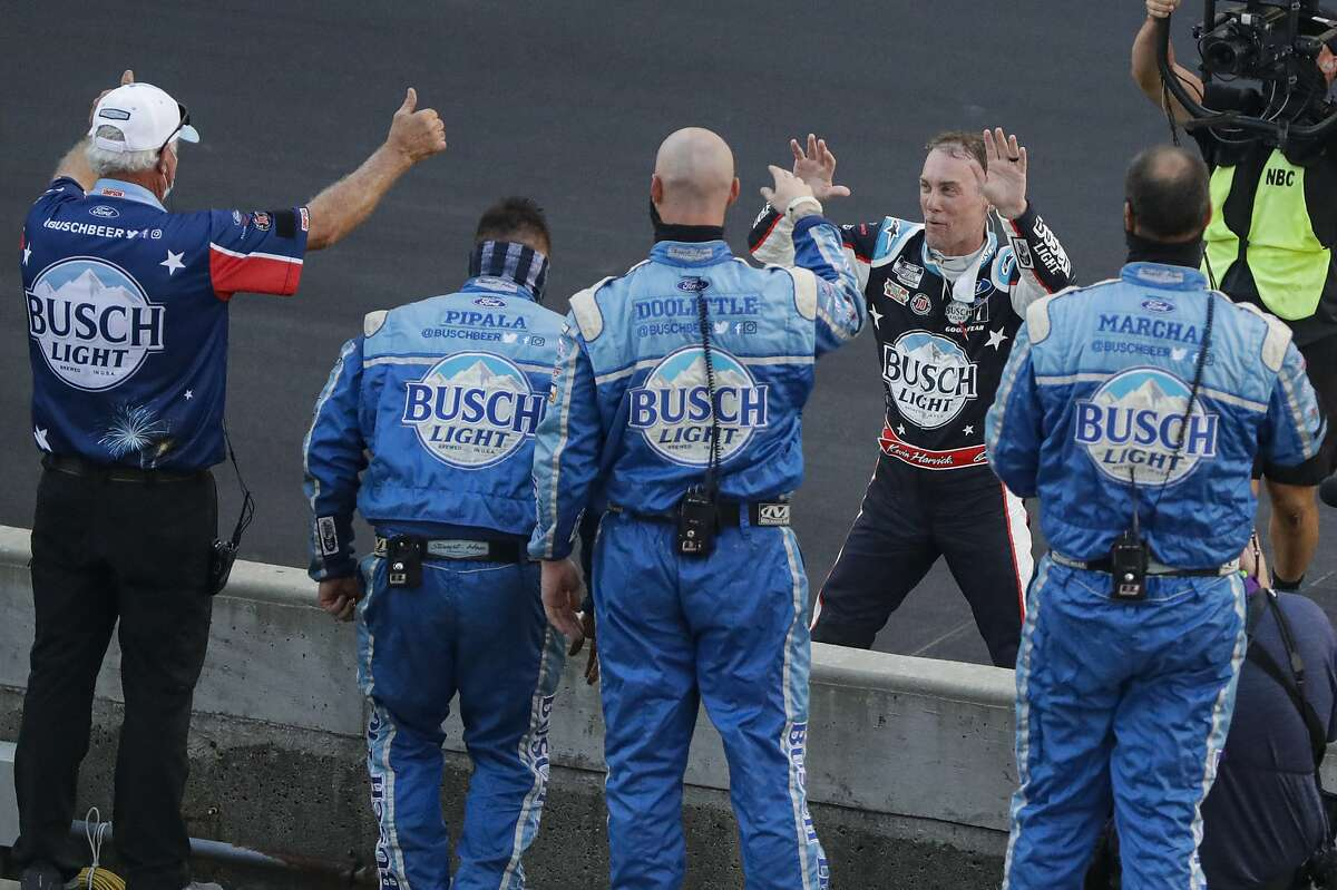 Kevin Harvick, on the far side of wall, won a NASCAR race in Indianapolis after beating Matt Kenseth off the final restart.