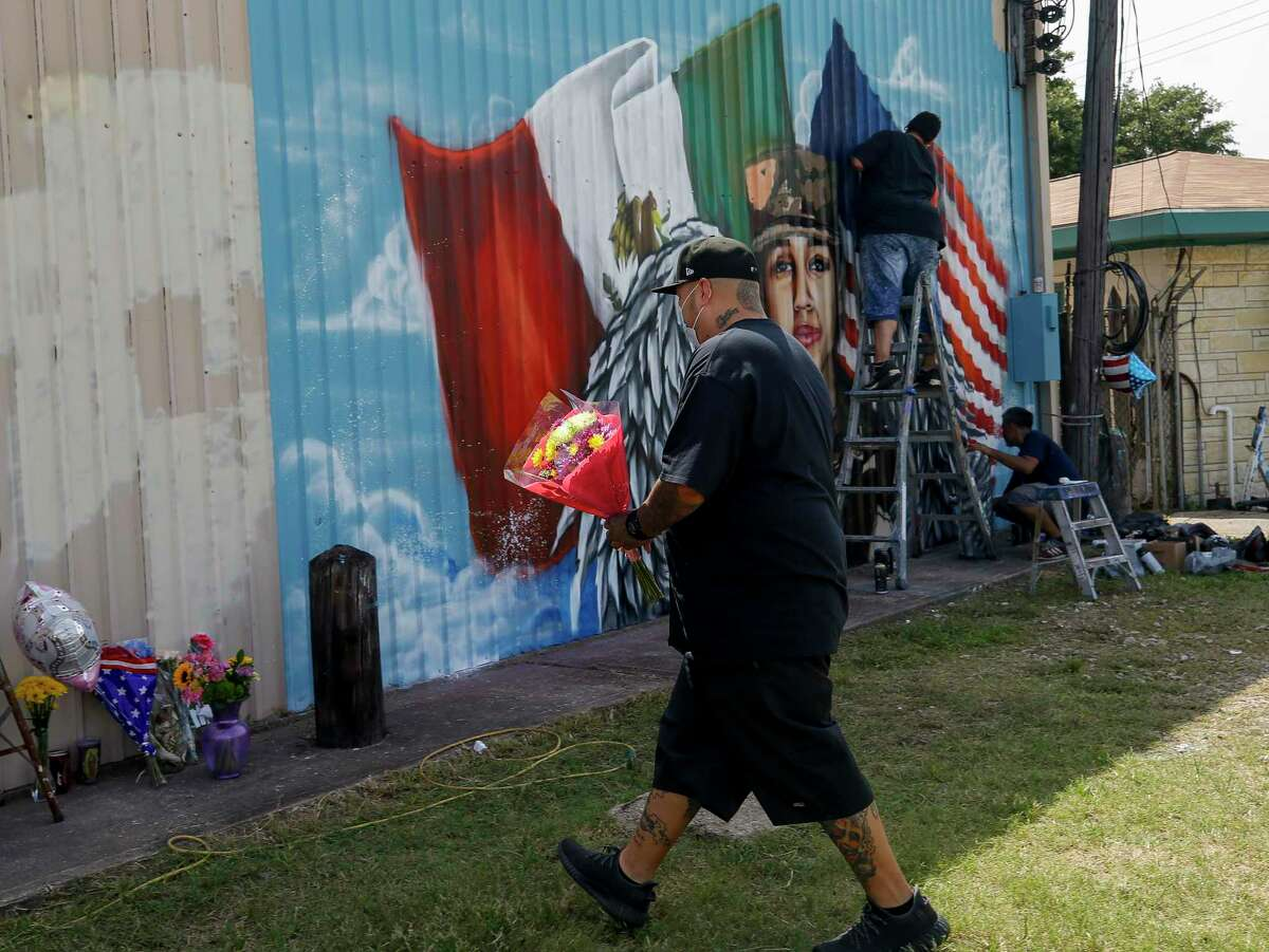 Zeke Gonzales drops off a bouquet of flowers at the site where artists were painting a mural honoring Houston native and Army Pfc. Vanessa Guillén on the back wall of Power House Gym on Sunday, July 5, 2020, in Houston. Guillén, 20, who went missing in April was presumably killed by a fellow soldier.