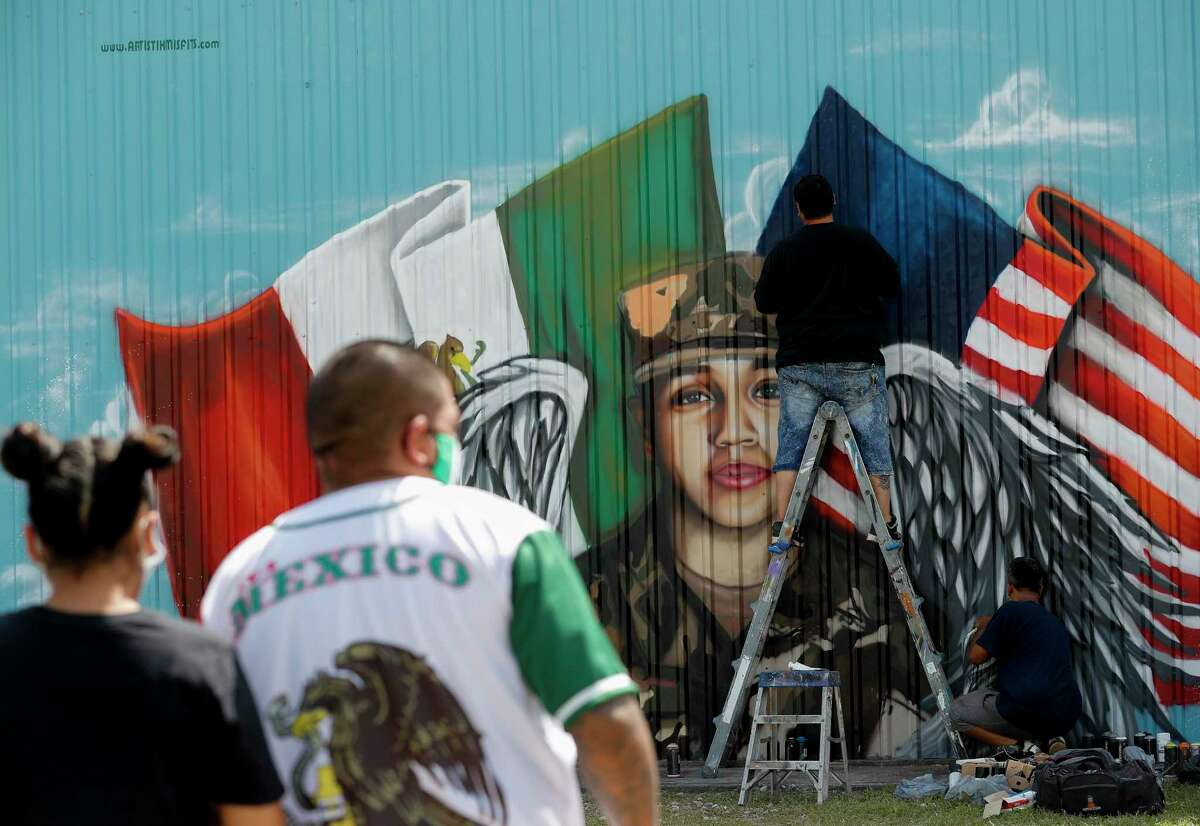 Artists Marcos Del Bosque, center, and Roland Saldaña, right, paint a mural honoring Houston native and Army Pfc. Vanessa Guillén on the back wall of Power House Gym on Sunday, July 5, 2020, in Houston. Guillén, 20, who went missing in April was presumably killed by a fellow soldier.