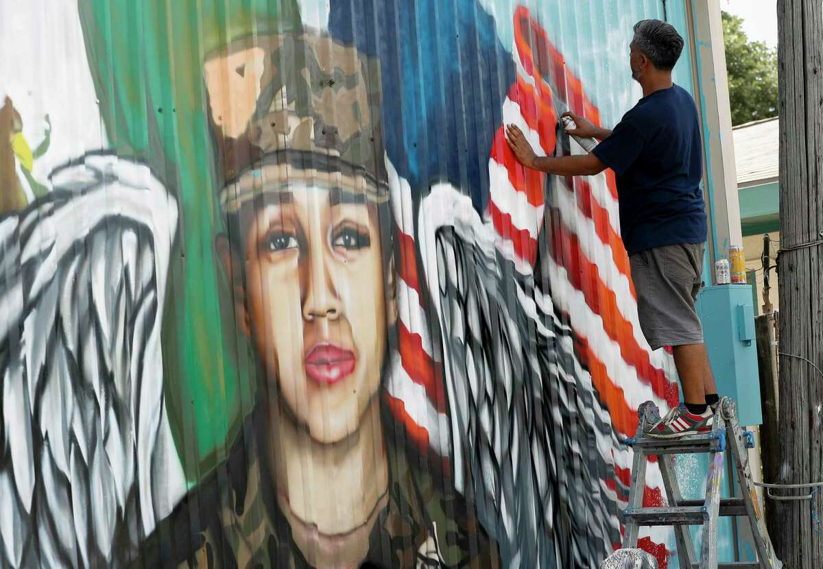 Artist Roland Saldaña paints a mural honoring Houston native and Army Pfc. Vanessa Guillén on the back wall of Power House Gym on Sunday, July 5, 2020, in Houston. Guillén, 20, who went missing in April was presumably killed by a fellow soldier.