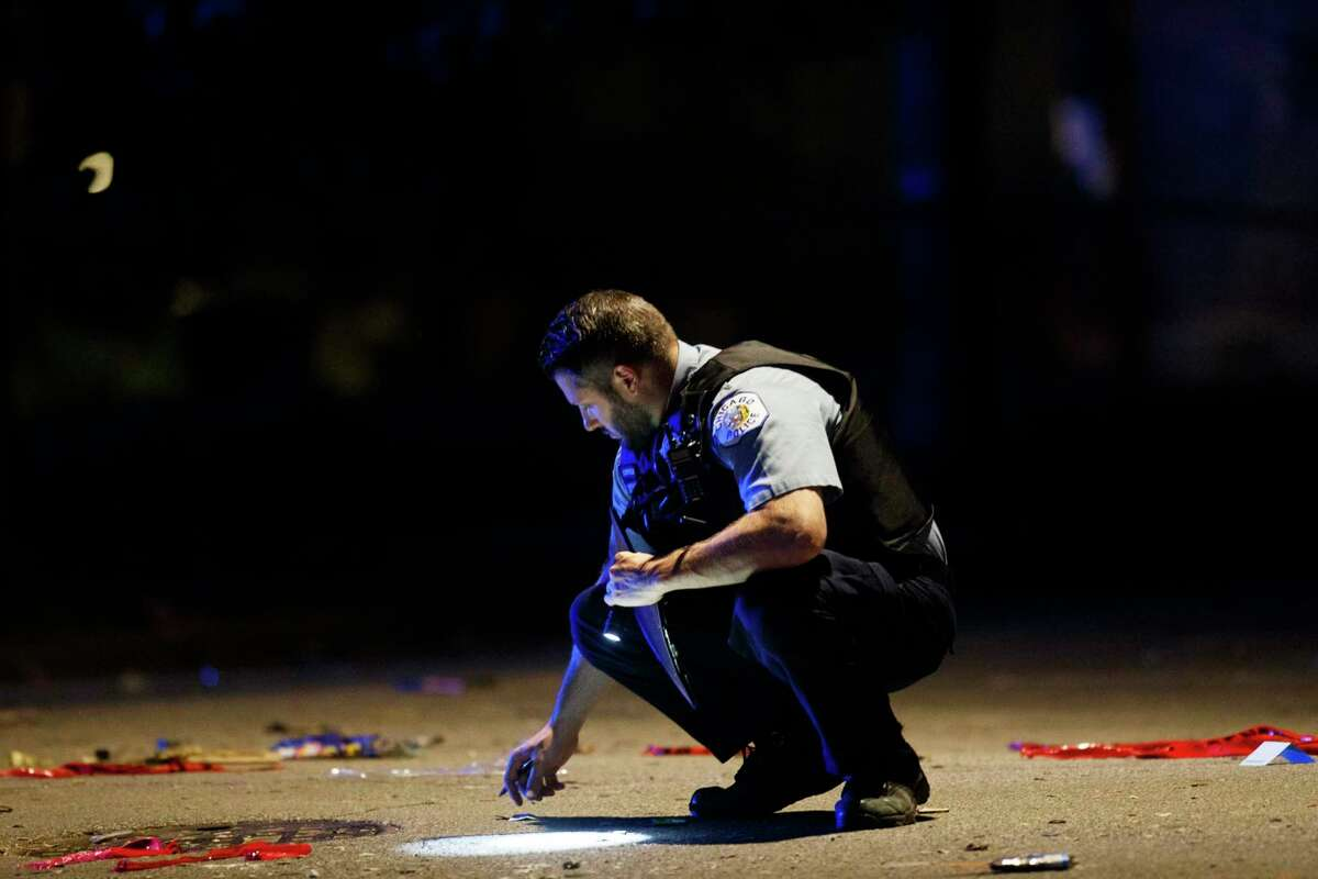 An officer investigates the scene of a shooting in Chicago on Sunday, July 5, 2020. At least a dozen people, including a 7-year-old girl at a family party and a teenage boy, were killed in Chicago over the Fourth of July weekend, police said. Scores of people were shot and wounded. (Armando L. Sanchez/Chicago Tribune via AP)