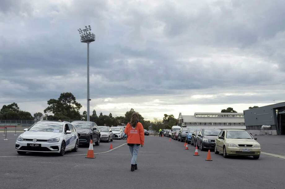 An information officer helps direct people at a drive-in Covid-19 testing site set up at the Melbourne Show Grounds in Melbourne, Victoria, Australia, on Jun 30, 2020. Photo: Bloomberg Photo By Carla Gottgens. / © 2020 Bloomberg Finance LP