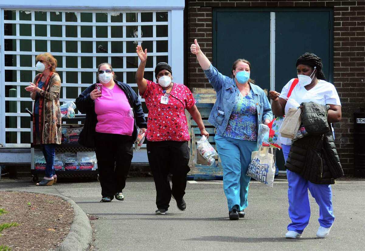 Health care workers wave during a cheer line set up to honor employees at the change-of-shift at Bishop Wicke nursing home on Long Hill Ave in Shelton, Conn., on Thursday May 14, 2020.