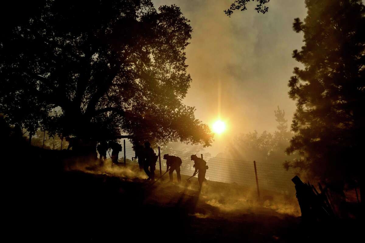 Firefighters battle the Crews Fire along Canada Road near Gilroy, Calif., Sunday, July 5, 2020.
