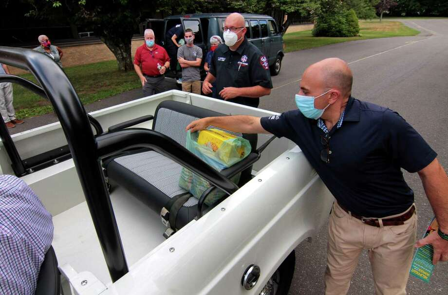 State Rep. Jason Perillo grabs a bag of donated food from a vehicle during a food drive for Spooner House of Shelton held at Elizabeth Shelton School in Shelton, Conn., on Wednesday July 1, 2020. State Rep. Perillo joined with State Sen. Kevin Kelly and State Rep. Ben McGorty who partnered with Echo Hose Ambulance to help collect for the Shelton homeless shelter. Photo: Christian Abraham / Hearst Connecticut Media / Connecticut Post