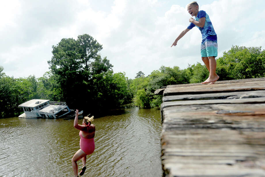 "Brody Lonion laughs as his mother Ashley Ply joins stepbrother Kaden Ply jumping from the old bridge that spans Cow Bayou near the boat launch beneath the Texas 87 bridge. Ashley Ply said jumping off the old bridge into the bayou is a long tradition for kids in the area. ""And especially now with places closed due to COVID-19, it's one of the only places kids have to swim"" during hot summer days, she says. Ply remembers many days spent with friends when she was a teen making the over 20-foot jump, but it took some prodding from her sons to join them now. ""I used to do this all the time when I was 16,"" she says, peering over the edge of the bridge to the water below. ""Wow, this is really high!"" She didn't remember it looking that high when she was a teen, she said. Eventually, the boys' pleas for her to join them in just one jump, and promises of a back massage and manicure, won her over, and the three made the jump together. Photo taken Tuesday, June 30, 2020 Kim Brent/The Enterprise Photo: Kim Brent/The Enterprise"