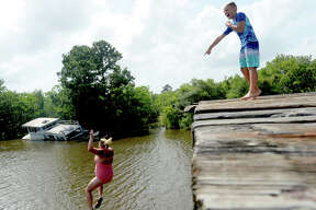 "Brody Lonion laughs as his mother Ashley Ply joins stepbrother Kaden Ply jumping from the old bridge that spans Cow Bayou near the boat launch beneath the Texas 87 bridge. Ashley Ply said jumping off the old bridge into the bayou is a long tradition for kids in the area. ""And especially now with places closed due to COVID-19, it's one of the only places kids have to swim"" during hot summer days, she says. Ply remembers many days spent with friends when she was a teen making the over 20-foot jump, but it took some prodding from her sons to join them now. ""I used to do this all the time when I was 16,"" she says, peering over the edge of the bridge to the water below. ""Wow, this is really high!"" She didn't remember it looking that high when she was a teen, she said. Eventually, the boys' pleas for her to join them in just one jump, and promises of a back massage and manicure, won her over, and the three made the jump together. Photo taken Tuesday, June 30, 2020 Kim Brent/The Enterprise"
