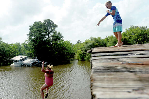 """Brody Lonion laughs as his mother Ashley Ply joins stepbrother Kaden Ply jumping from the old bridge that spans Cow Bayou near the boat launch beneath the Texas 87 bridge. Ashley Ply said jumping off the old bridge into the bayou is a long tradition for kids in the area. """"And especially now with places closed due to COVID-19, it's one of the only places kids have to swim"""" during hot summer days, she says. Ply remembers many days spent with friends when she was a teen making the over 20-foot jump, but it took some prodding from her sons to join them now. """"I used to do this all the time when I was 16,"""" she says, peering over the edge of the bridge to the water below. """"Wow, this is really high!"""" She didn't remember it looking that high when she was a teen, she said. Eventually, the boys' pleas for her to join them in just one jump, and promises of a back massage and manicure, won her over, and the three made the jump together. Photo taken Tuesday, June 30, 2020 Kim Brent/The Enterprise"""