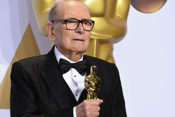 """Ennio Morricone poses with his Oscar for best original score for """"The Hateful Eight"""" in 2016. One of the world's best-known and most prolific film composers, Morricone has died in Rome."""