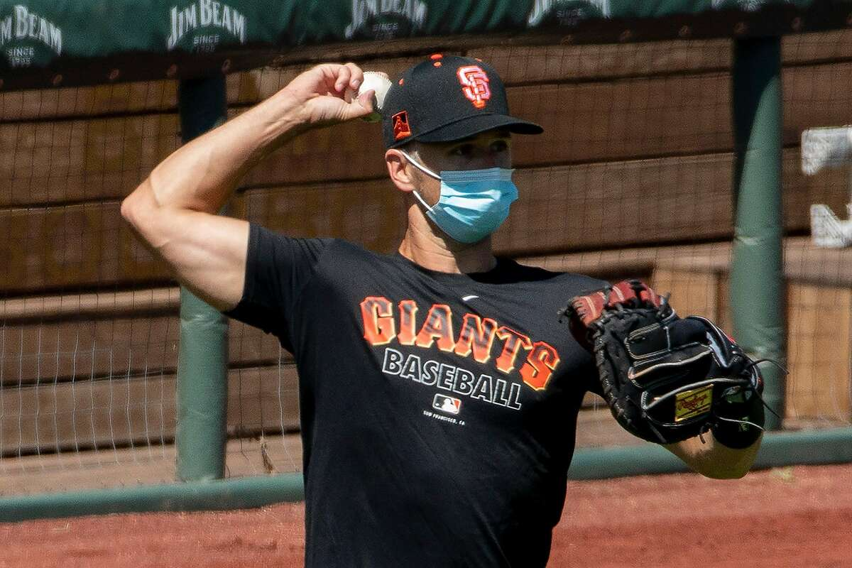 San Francisco Giants catcher Buster Posey (#28) wears a mask while throwing a ball during the San Francisco Giants' summer training camp session at Oracle Park in San Francisco, Calif. Saturday, July 4, 2020. Due to COVID-19, the 2020 MLB season has been postponed with players just beginning to return for warmups and practices while wearing masks and keeping social distance.