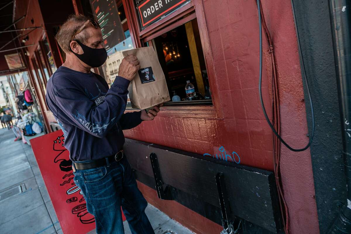 Lusiron Silvira, a driver for Postmates, which has added Prop. 22 fees, picks up an order from Popsons Burgers in San Francisco in June.