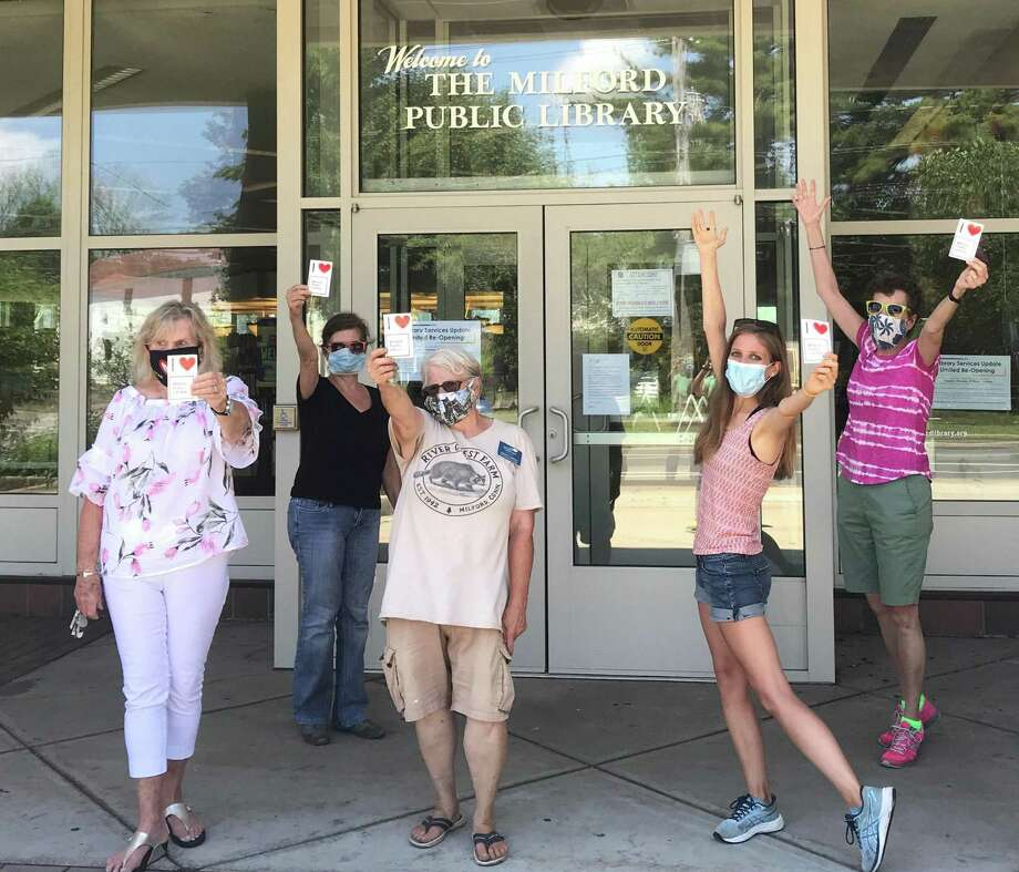 Judy Kennedy, PaulaGoncalves, Cheryl Cappiali, Ahsley Volkens and Amy Bringardner pose in front of the Milford Public Library with their window clings. Photo: Milford Public Library