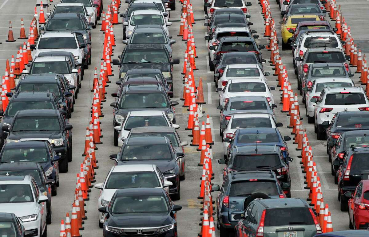 Lines of cars wait at a drive-through coronavirus testing site, Sunday, July 5, 2020, outside Hard Rock Stadium in Miami Gardens, Fla. Florida health officials say the state has reached a grim milestone: more than 200,000 people have tested positive for the novel coronavirus since the start of the outbreak.