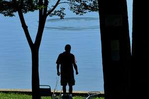 A fisherman watches ripples in the water as he fishes in Iroquois Lake in Central Park on Monday, July 6, 2020 in Waterford, N.Y. (Lori Van Buren/Times Union)