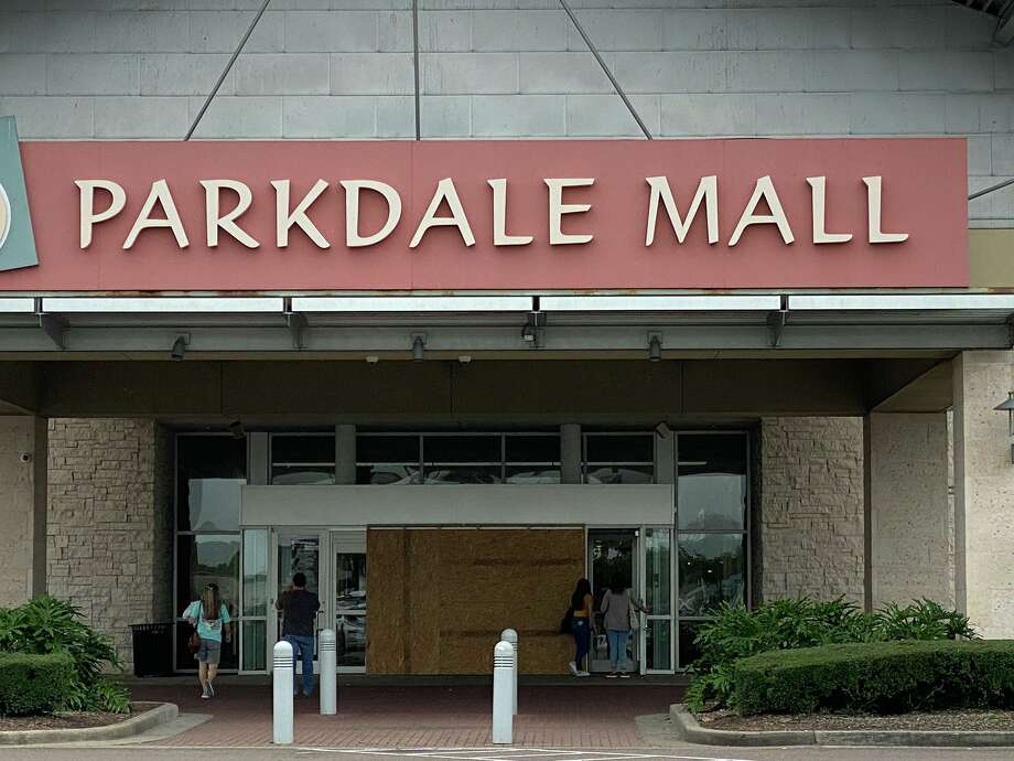 Shopper walk through side doors to the Parkdale Mall entry Monday, where a car drove through the glass doors Sunday morning. Boards cover the automatic doors that were shattered in the crash. Photo: Kim Brent/ Beaumont Enterprise