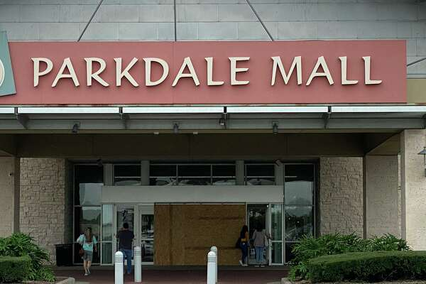 Shopper walk through side doors to the Parkdale Mall entry Monday, where a car drove through the glass doors Sunday morning. Boards cover the automatic doors that were shattered in the crash.