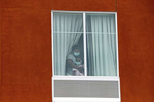 An asylum-seeking Haitian mother and her 3-year-old daughter look out the window of the room at a Homewood Suites by Hilton in San Antonio where they were being held by Immigration and Customs Enforcement on July 1, 2020. The father and son, 7, in the family are being held in a separate room.