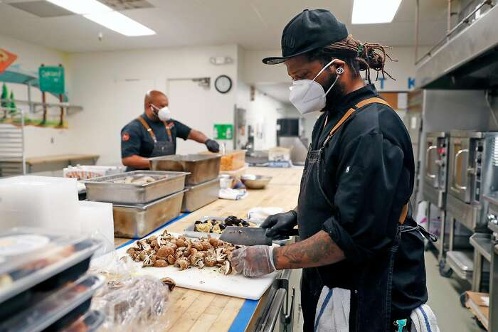 Chef Joseph Hall (right) and Montperi Catering owner Lamont Perriman prep meals for delivery at Port Kitchens in Oakland, Calif., on Wednesday, July 2, 2020. The Bay Area hospitality industry is just 3% Black and the chefs and servers of color have endured a history of discrimination.