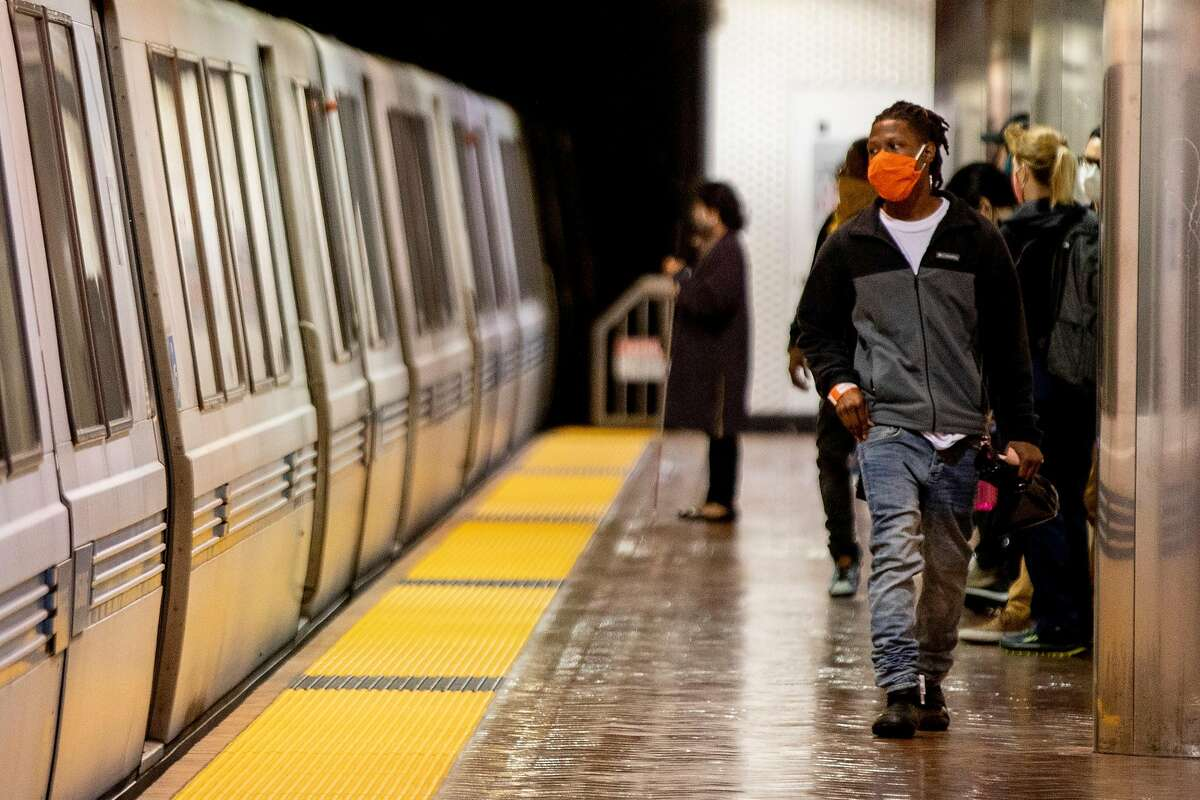 Riders wear face masks while waiting for their trains at Powell Street BART Station in in San Francisco, Calif. Friday, June 26, 2020. People returning to public transportation can expect mandatory face coverings for riders and operators, physical distancing markers and limited capacity on all vehicles. BART has a 15-step plan to welcome back riders that includes using hospital-grade disinfectant in stations and on-board trains, running longer cars to help promote social distancing, and offering personal hand straps for purchase that riders can take home and wash.