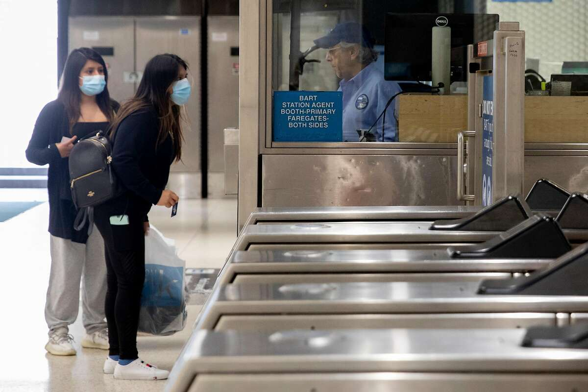A station attendant assists two masked riders while at Powell Street BART Station in in San Francisco, Calif. Friday, June 26, 2020. People returning to public transportation can expect mandatory face coverings for riders and operators, physical distancing markers and limited capacity on all vehicles. BART has a 15-step plan to welcome back riders that includes using hospital-grade disinfectant in stations and on-board trains, running longer cars to help promote social distancing, and offering personal hand straps for purchase that riders can take home and wash.