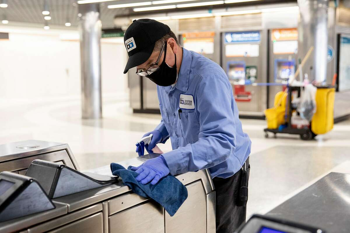 BART custodian David Ho disinfects turnstiles in June at Powell Street BART Station in S.F. With ridership suffering due to the coronavirus, BART may offer buyouts to 1,662 eligible for early retirement.