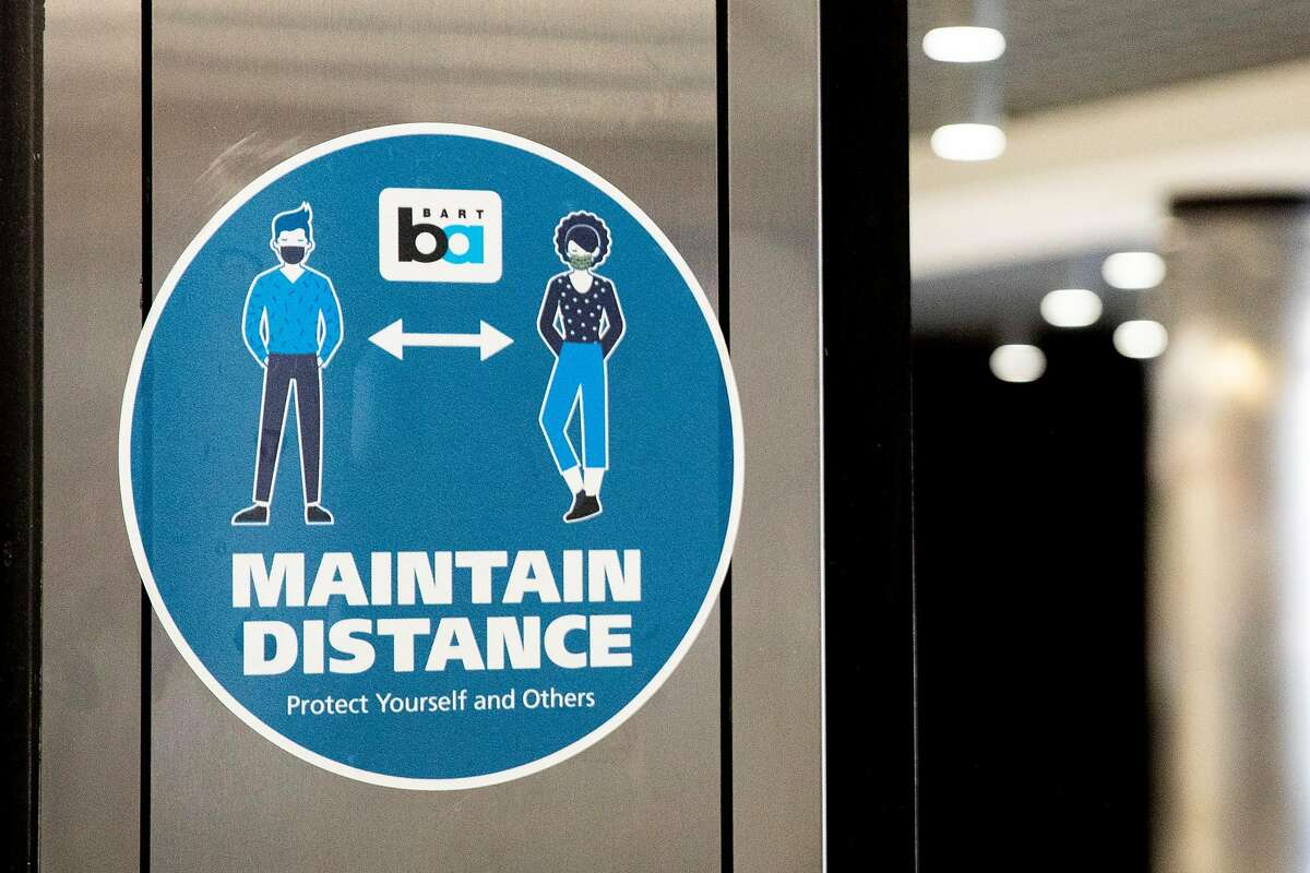 A sign encourages riders to socially distance while standing at Powell Street BART Station in in San Francisco, Calif. Friday, June 26, 2020. People returning to public transportation can expect mandatory face coverings for riders and operators, physical distancing markers and limited capacity on all vehicles. BART has a 15-step plan to welcome back riders that includes using hospital-grade disinfectant in stations and on-board trains, running longer cars to help promote social distancing, and offering personal hand straps for purchase that riders can take home and wash.