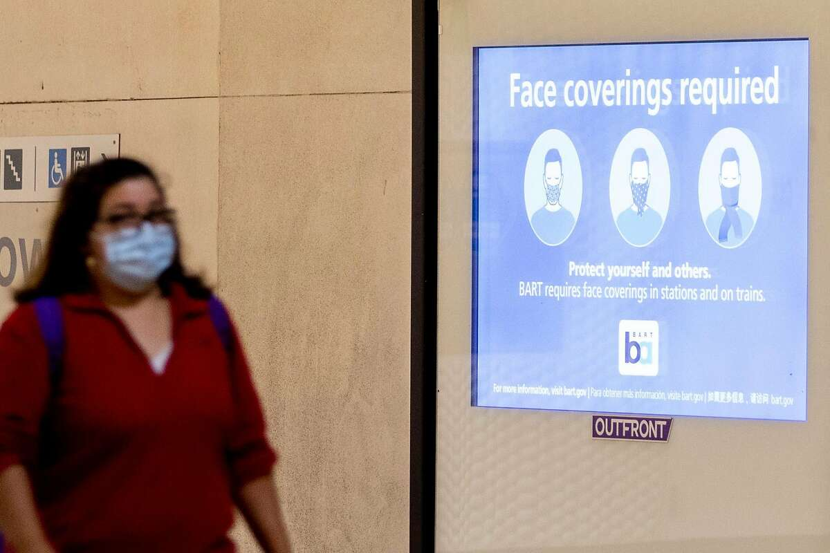 A sign reminds riders to wear face masks while waiting for their trains at Powell Street BART Station in in San Francisco, Calif. Friday, June 26, 2020. People returning to public transportation can expect mandatory face coverings for riders and operators, physical distancing markers and limited capacity on all vehicles. BART has a 15-step plan to welcome back riders that includes using hospital-grade disinfectant in stations and on-board trains, running longer cars to help promote social distancing, and offering personal hand straps for purchase that riders can take home and wash.