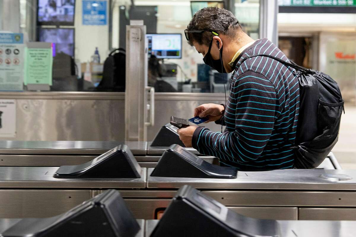 A rider wears a face mask while tapping their Clipper Card at Powell Street BART Station in in San Francisco, Calif. Friday, June 26, 2020. State Assemblyman David Chiu is re-introducing a bill that seeks to create an integrated public transportation system in the Bay Area and solve issues brought on by the fragmentation of the area's various public transportation systems in an effort to increase ridership.