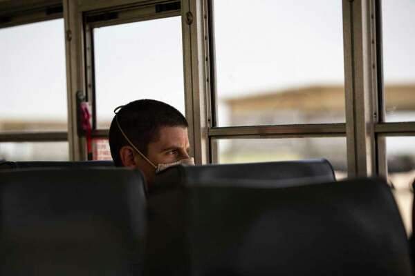 Lt. Col. J.C. Gorman rides a bus to the flight line on Joint Base San Antonio-Randolph last month. Training pilots has gotten complicated since the onset of the coronavirus. Essential personnel are the only ones allowed in the typically busy squadron.