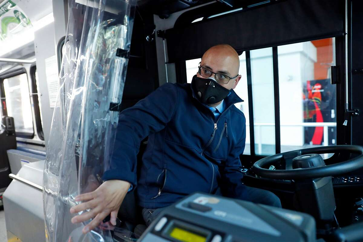 Luis Licea moves a moisture barrier before operating a Golden Gate Transport bus in San Francisco, Calif., on Wednesday, June 24, 2020. People returning to public transportation can expect familiar safety protocols used on recommendations from the CDC. Those include mandatory face coverings for riders and operators, physical distancing markers and limited capacity on all vehicles.