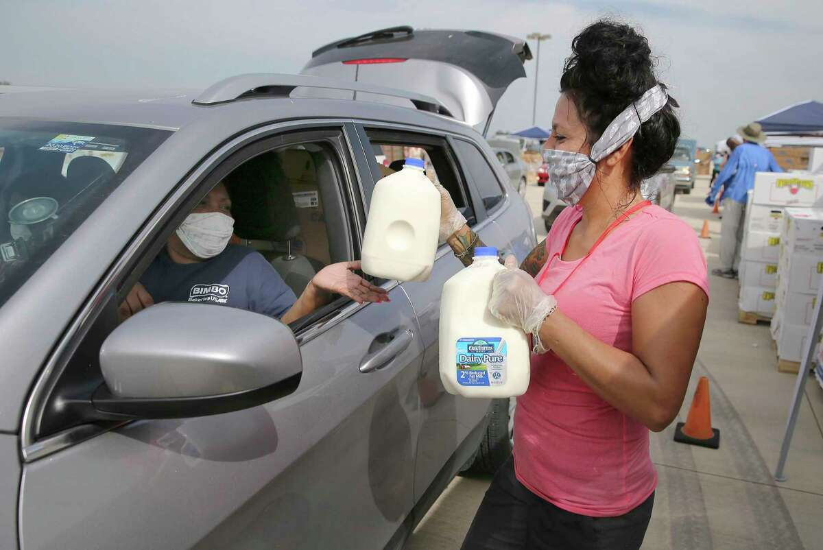 Heather Martinez greets one of the families that had been waiting for hours in a miles-long line at the San Antonio Food Bank distribution event at Traders Village April 9, handing them two gallons of milk. Martinez is one of many volunteers who have stepped up to help the Food Bank; but more are needed as the pandemic continues to wreak economic havoc on the community.