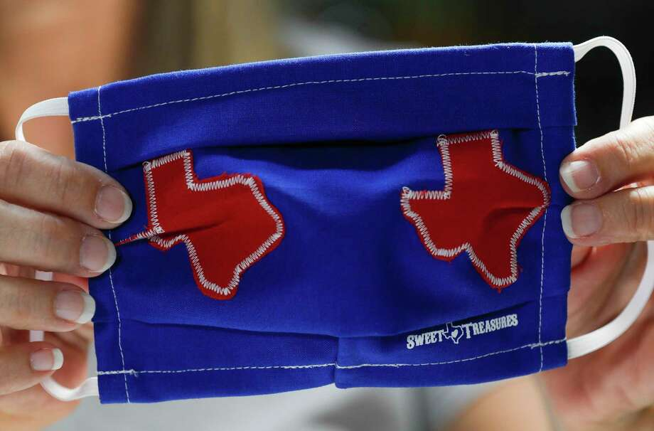 Toni Rodriguez checks the stitching on the back of a custom Texas-themed mask at Sweet Texas Treasures Boutique, Friday, July 3, 2020, in Montgomery. Gov. Greg Abbott's statewide face-covering order, which targets Texan counties with more than 20 coronavirus cases, went into effect at noon in an effort to slow the spread of COVID-19. Photo: Jason Fochtman, Houston Chronicle / Staff Photographer / 2020 © Houston Chronicle