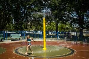 Isabella Celletti of Illinois, 7, runs through a fountain at the Gerstacker Spray Park Monday, July 6, 2020 in downtown Midland. (Katy Kildee/kkildee@mdn.net)