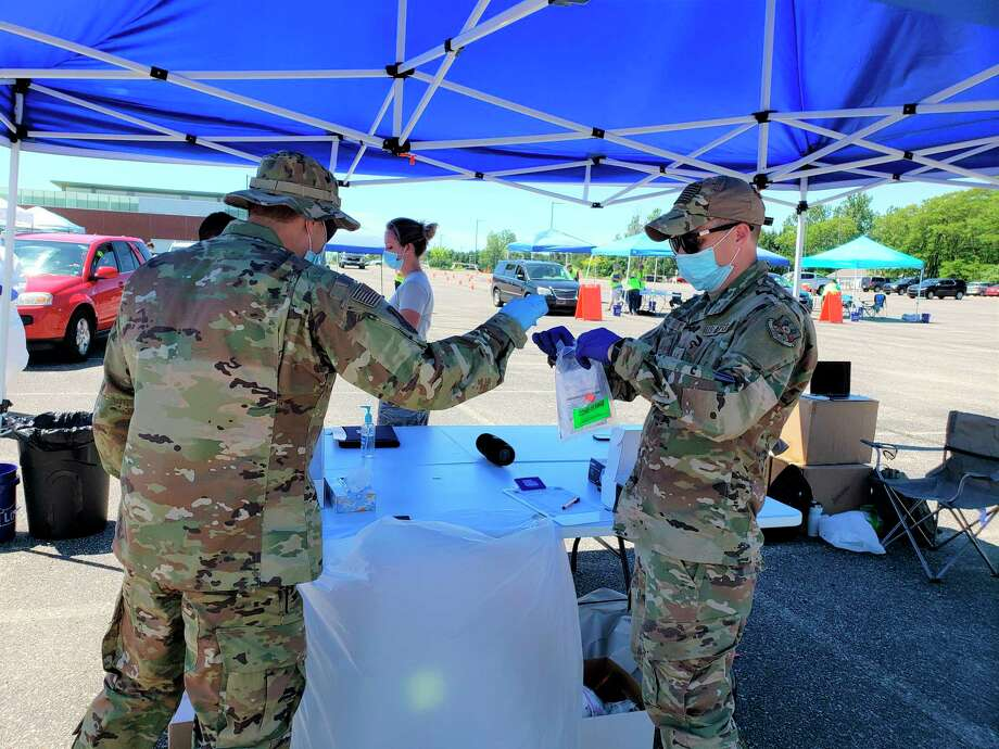 Members of the National Guard took nasopharyngeal swab samples at a COVID-19 screening event at the Manistee High School parking lot last month. (File photo)