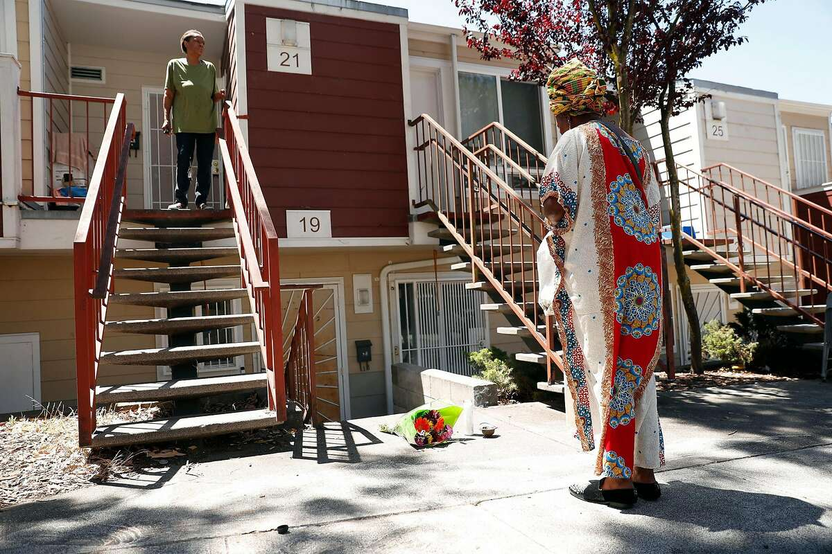 Asale-Haquekyah Chandler (right), the mother of Yalani Chinyamurindi, who was fatally shot in 2015, stands in silence after laying flowers and lighting a candle at the scene of the July 4th fatal shooting of 6-year-old Jace Young on Whitfield Court in San Francisco, Calif., on Monday, July 6, 2020.